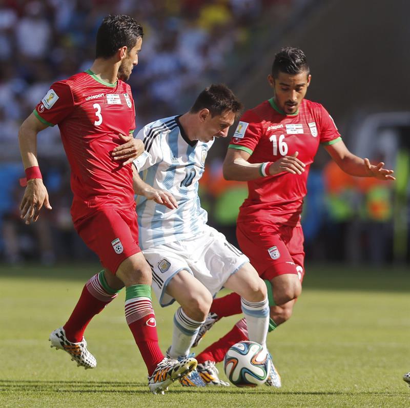 El delantero argentino Lionel Messi (c) con el balón ante los jugadores iraníes Jalal Hosseini (i) . EFE