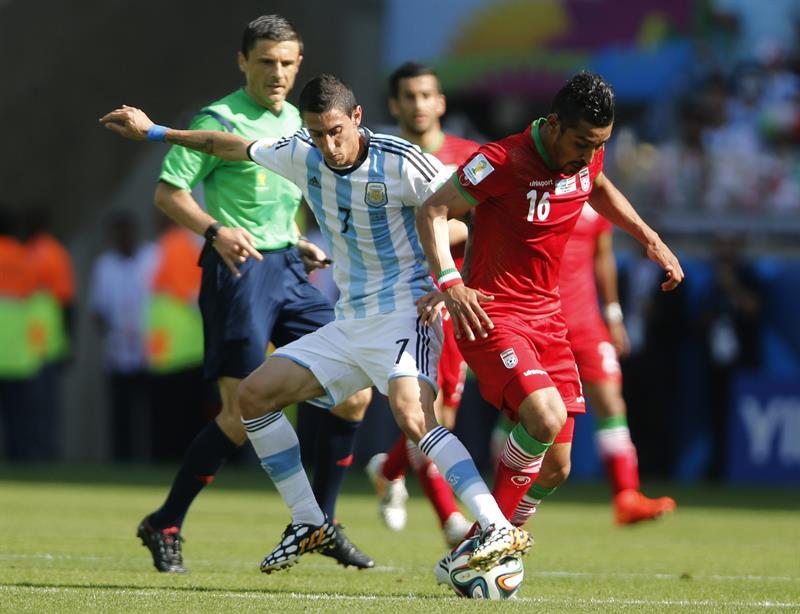 El centrocampista argentino Ángel di María (i) lucha un balón con el delantero iraní Reza Ghoochannejad. EFE