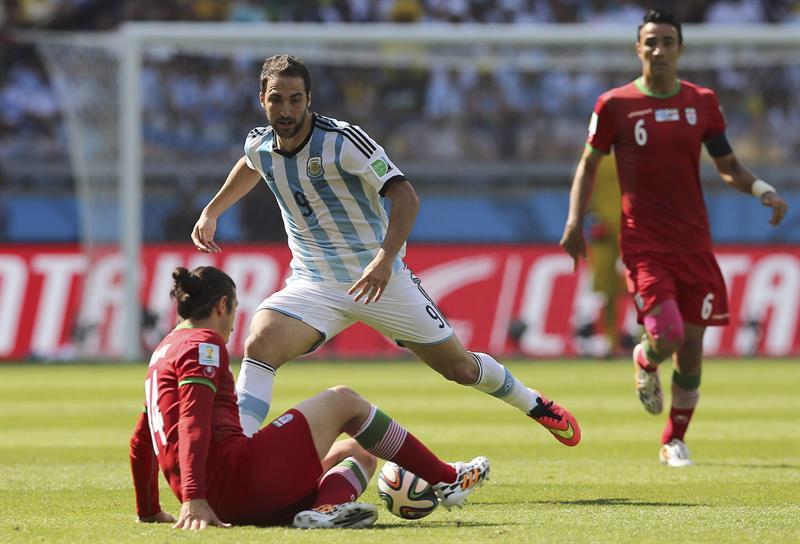 El delantero argentino Gonzalo Higuaín (d) lucha un balón con el centrocampista iraní Andranik Timotian (i). EFE