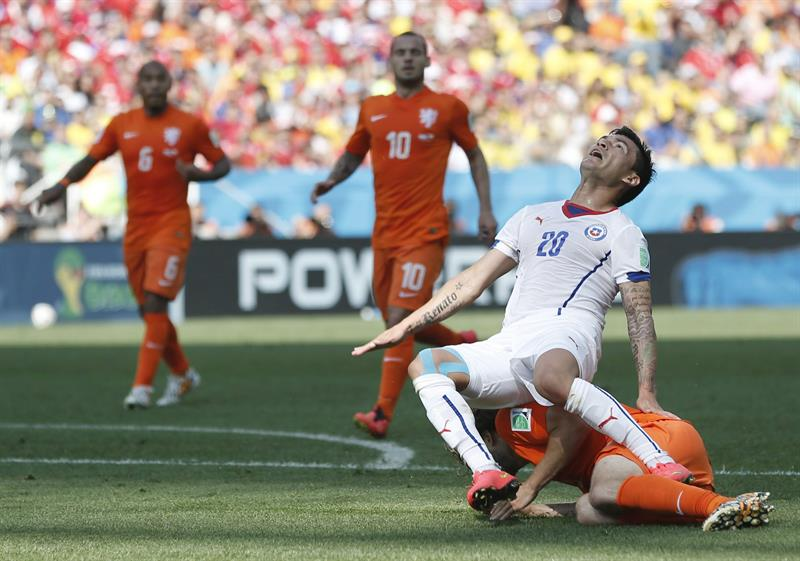 Charles Aranguiz of Chile is tackled during the FIFA World Cup 2014 group B preliminary round match between the Netherlands and Chile. EFE