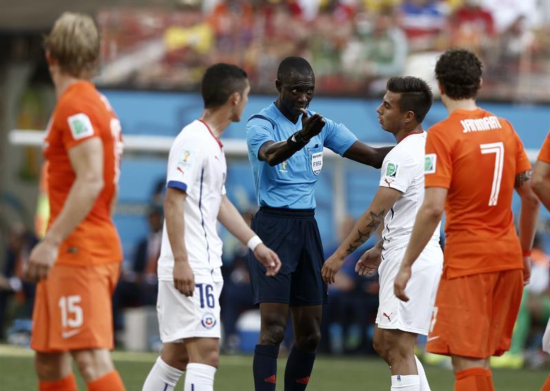 El árbitro Bakary Gassama (c) ante delantero chileno Eduardo Vargas (2d) durante el partido Holanda-Chile, del Grupo B. EFE