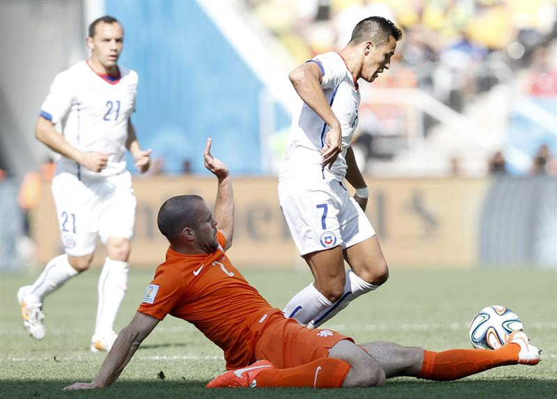 Ron Vlaar (C) of the Netherlands in action with Alexis Sanchez (R) of Chile during the FIFA World Cup 2014 group B. EFE