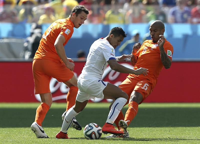 El delantero chileno Alexis Sánchez (c) con el balón ante los jugadores holandeses Nigel De Jong (d) y Daley Blind durante el partido. EFE