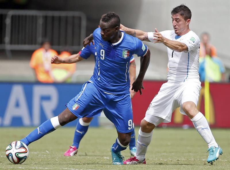 Italy's Mario Balotelli (L) and Uruguay's Christian Rodriguez (R) vie for the ball during the FIFA World Cup 2014 group D. EFE