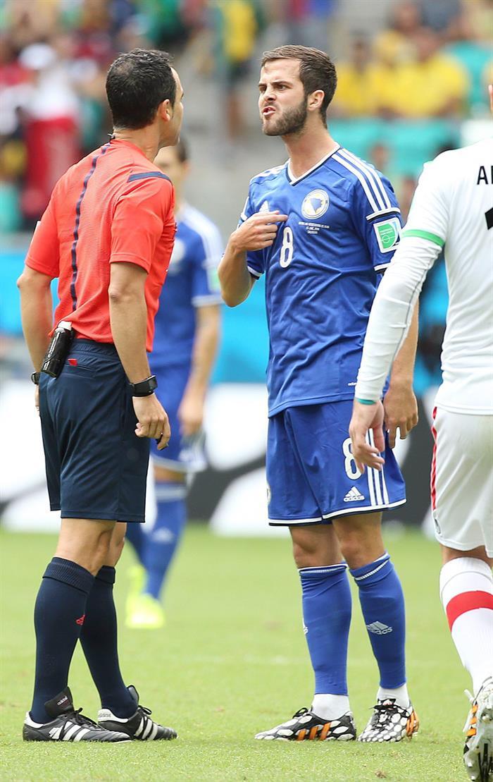 Miralem Pjanic of Bosnia-Herzegovina (R) argues with referee Carlos Velasco Carballo of Spain. EFE