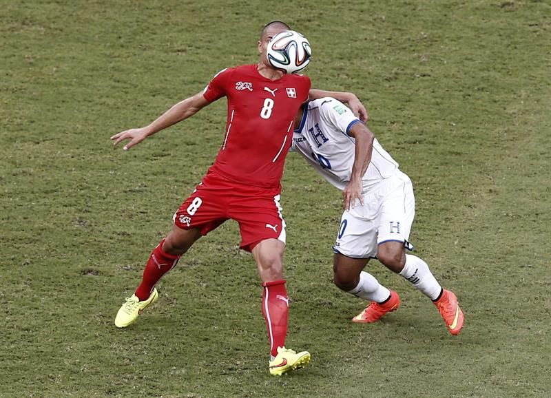El centrocampista suizo Gokhan Inler (i) lucha un balón con el centrocampista hondureño Jorge Claros,. EFE