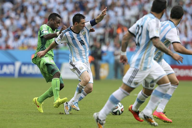 El delantero argentino Lionel Messi (2i) con el balón ante el centrocampista nigeriano Ogenyi Onazi, durante el partido Nigeria-Argentina. EFE
