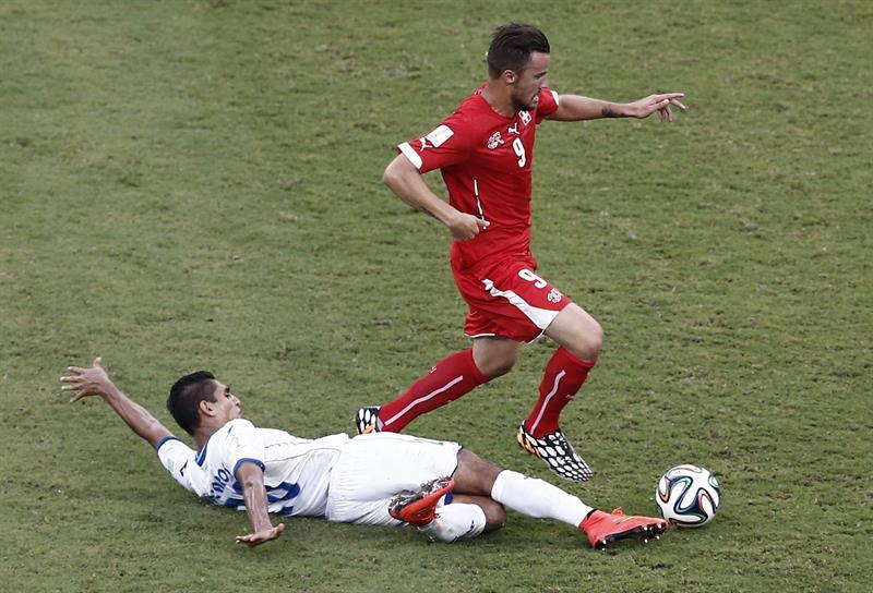 El delantero suizo Haris Seferovic (d) avanza con el balón ante el centrocampista hondureño Jorge Claros. EFE