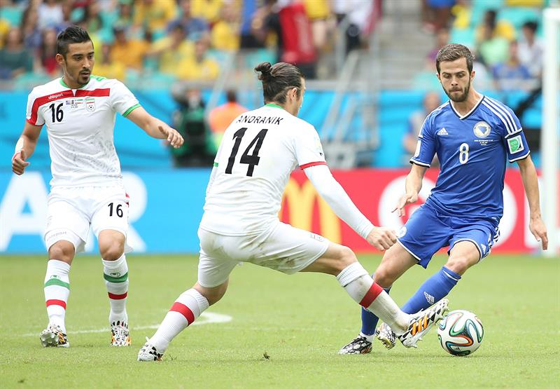 Miralem Pjanic of Bosnia-Herzegovina (R) and Andranik Timotian of Iran (C) in action during the FIFA World Cup 2014 group F. EFE