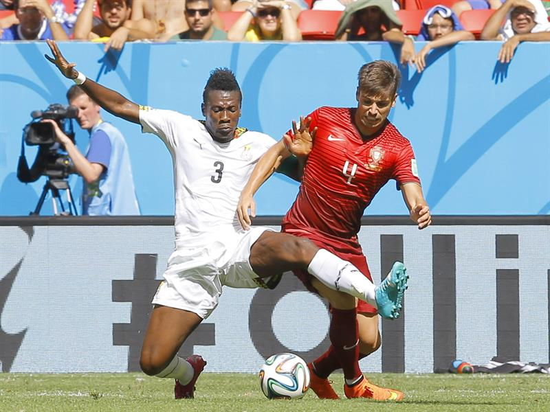 Asamoah Gyan (L) of Ghana in action with Miguel Veloso of Portugal during the FIFA World Cup 2014 group G. EFE