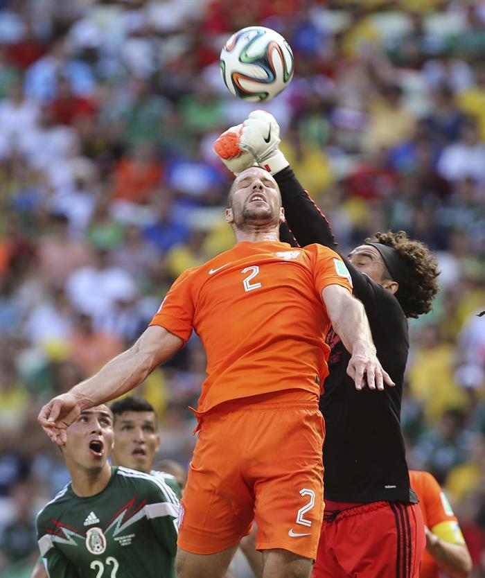El guardameta mexicano Guillermo Ochoa (d) despeja de puños ante el defensa holandés Ron Vlaar. EFE