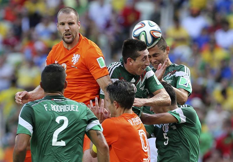 El centrocampista mexicano Héctor Herrera (2d) intenta rematar de cabeza ante el defensa holandés Ron Vlaar . EFE