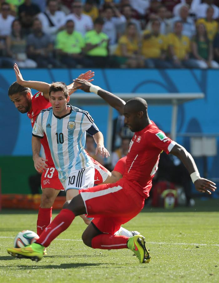 Lionel Messi (C) of Argentina in action with Johan Djourou (R) of Switzerland during the FIFA World Cup 2014. EFE