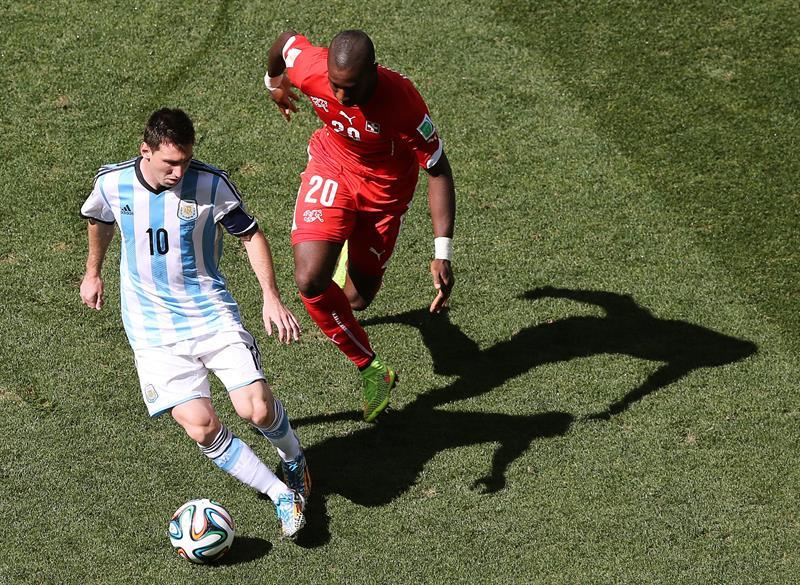 El delantero argentino Lionel Messi (i) controla el balón ante el defensa suizo Johan Djourou. EFE