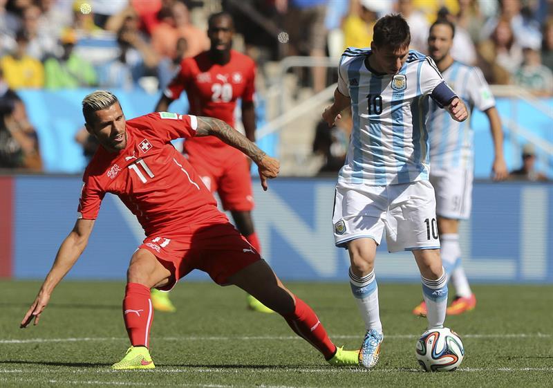 El delantero argentino Lionel Messi (d) controla el balón ante la oposición del centrocampista suizo Valon Behrami. EFE