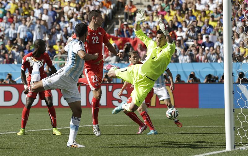 El defensa argentino Ezequiel Garay (i) remata ante el guardameta suizo Diego Benaglio (d). EFE