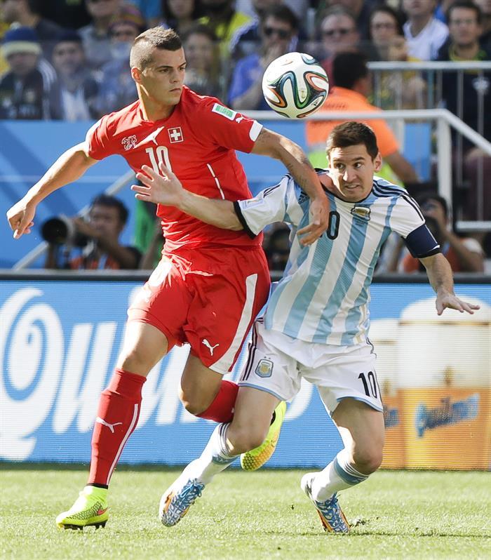 El delantero argentino Lionel Messi (d) lucha un balón con el centrocampista suizo Granit Xhaka (i). EFE