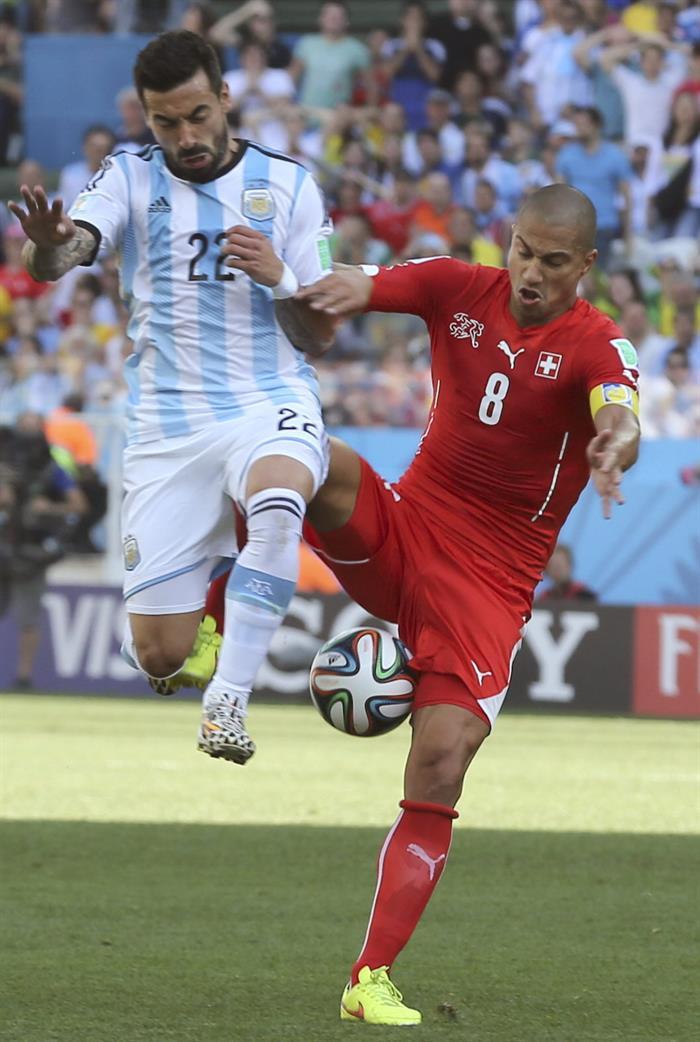 El delantero argentino Ezequiel Lavezzi (i) y el centrocampista suizo Gokhan Inler luchan por el balón. EFE