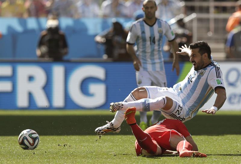 El delantero argentino Ezequiel Lavezzi (arriba) lucha un balón con el centrocampista suizo Xherdan Shaqiri. EFE