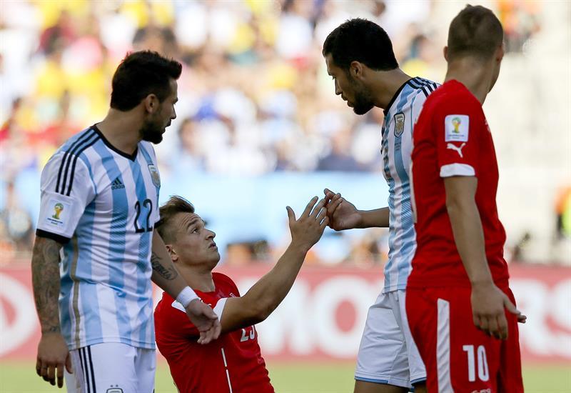 El centrocampista suizo Xherdan Shaqiri (2i) conversa con el defensa argentino Ezequiel Garay (2d). EFE