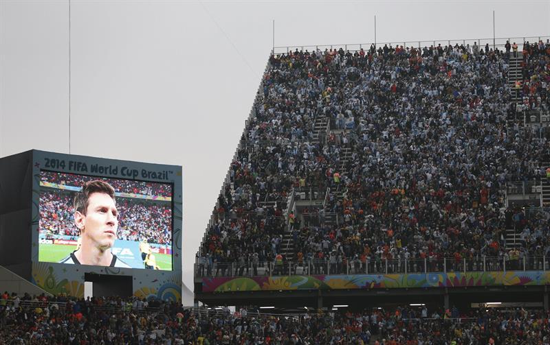 Miles de aficionados observan la imagen del delantero argentino Lionel Messi en una gran pantalla antes del inicio del partido. Foto: EFE