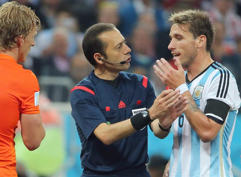 Referee Cueneyt Cakir of Turkey (C) talks to Lucas Biglia of Argentina (R) during the FIFA World Cup 2014. EFE