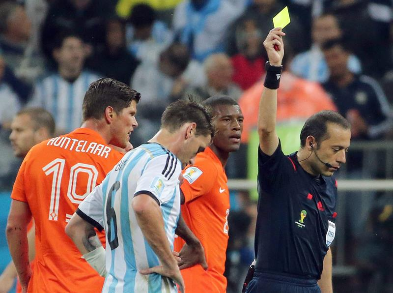 Referee Cueneyt Cakir of Turkey shows the yellow card to Klaas-Jan Huntelaar of the Netherlands during the FIFA World Cup 2014. EFE