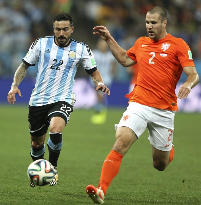 El delantero argentino Ezequiel Lavezzi (i) lucha un balón con el defensa holandés Ron Vlaar (d). Foto: EFE