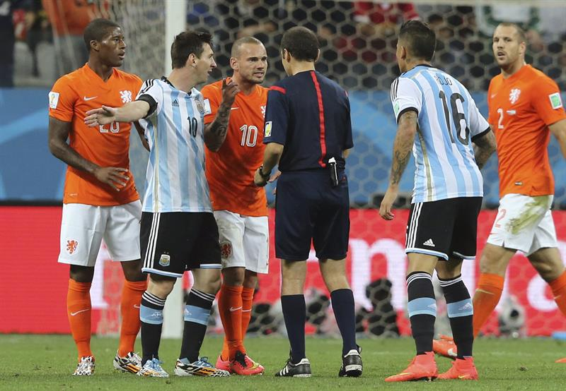 El delantero argentino Lionel Messi y el centrocampista holandés Wesley Sneijder conversan con el árbitro turco Cüneyt Cakir. Foto: EFE
