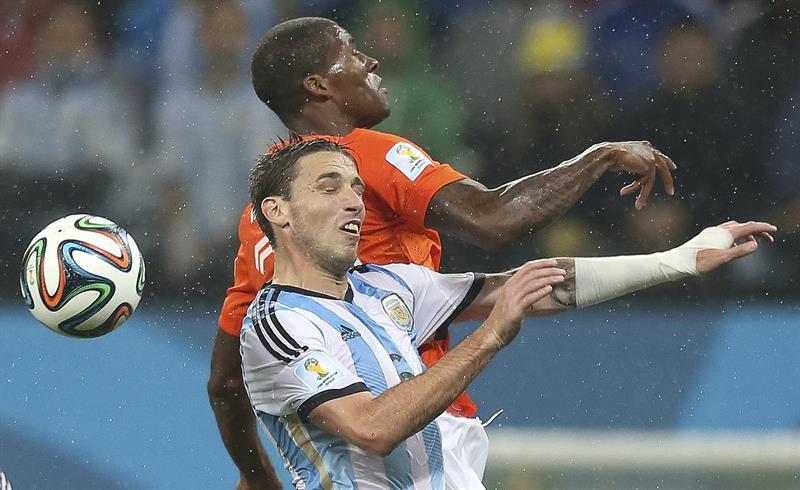 El centrocampista argentino Lucas Biglia (c) lucha un balón ante el centrocampista holandés Georginio Wijnaldum (detrás). Foto: EFE