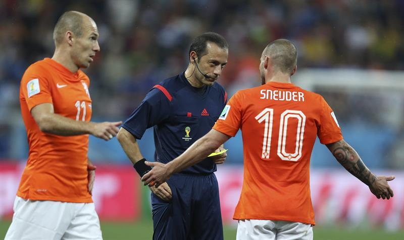 El centrocampista holandés Wesley Sneijder (d) conversa con el árbitro turco, Cüneyt Cakir, ante el delantero holandés Arjen Robben. Foto: EFE