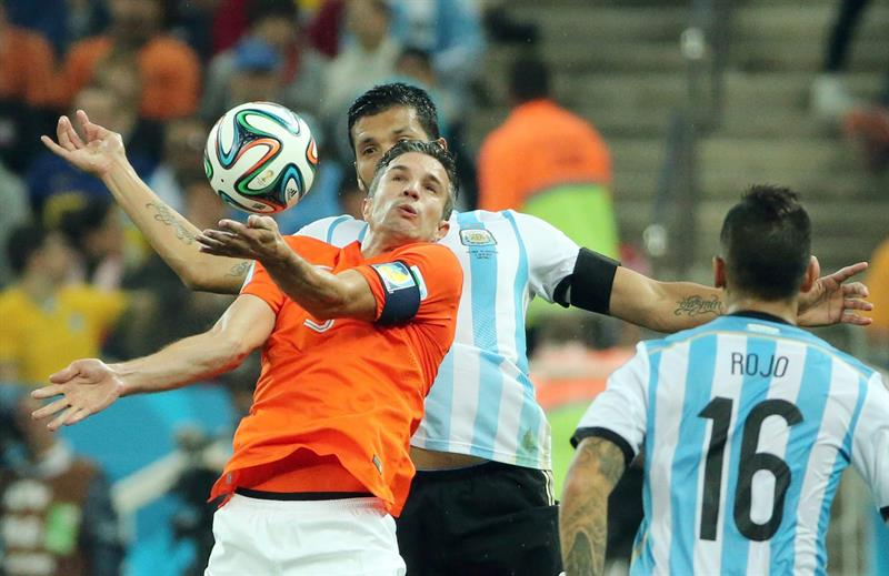 Robin van Persie of the Netherlands (front) and Ezequiel Garay of Argentina (behind) in action during the FIFA World Cup 2014. EFE