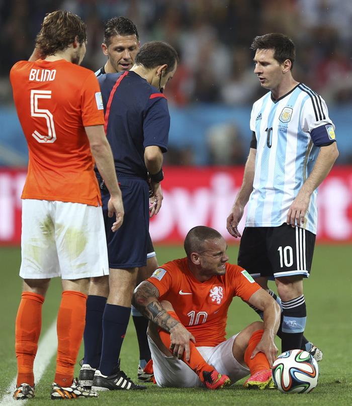 El centrocampista holandés Wesley Sneijder (2d) tendido sobre el terreno de juego ante el delantero argentino Lionel Messi. Foto: EFE