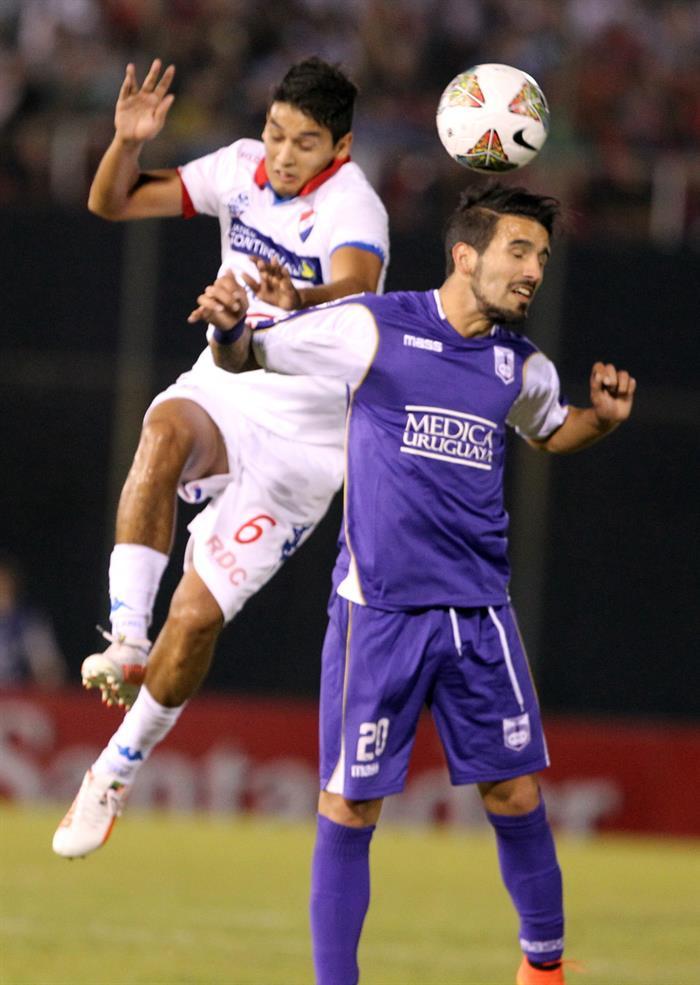 El jugador del Defensor Sporting de Uruguay Mathias Cardaccio (d) pelea el balón con Silvio Torales (i), del Nacional de Paraguay. EFE