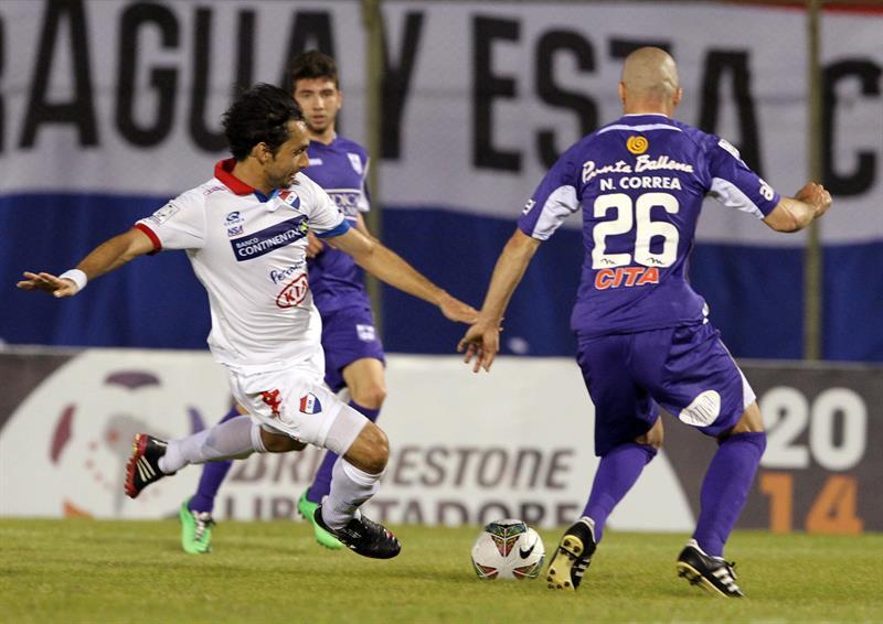 El jugador del Defensor Sporting de Uruguay, Nicolás Correa (d) pelea el balón con David Bernardo Mendoza (i), del Nacional de Paraguay. EFE