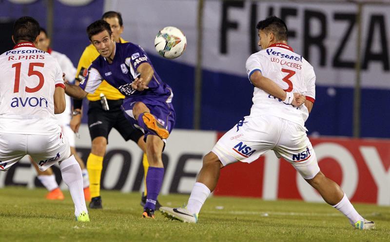 El jugador del Defensor Sporting Matías Alonso (c) patea el balón ante la marca de Leonardo Cáceres (d) y Raúl Piris (i), de Nacional. EFE