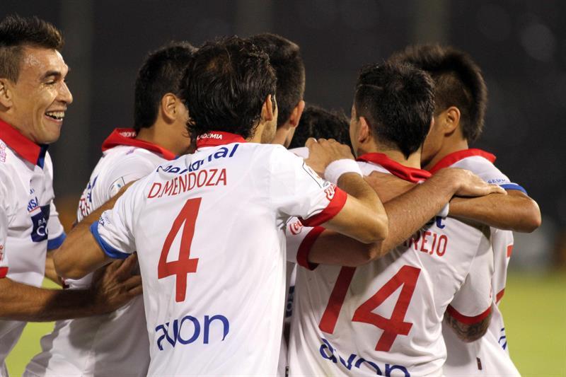 Jugadores de Nacional celebran después de anotar un gol ante Defensor Sporting. EFE