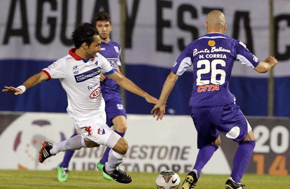 El jugador del Defensor Sporting de Uruguay, Nicolás Correa (d) pelea el balón. Foto: EFE