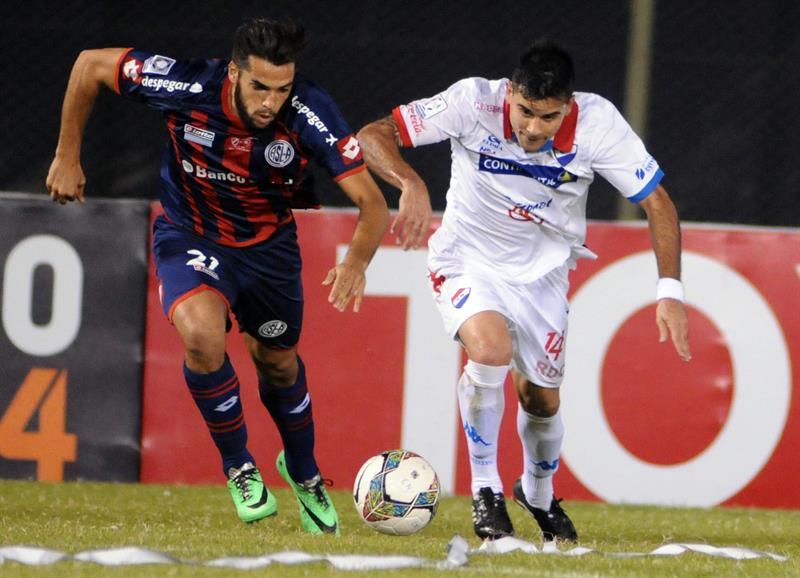 El jugador de San Lorenzo Juan Mercier (i) disputa el balón con David Mendoza (d) de Nacional. EFE