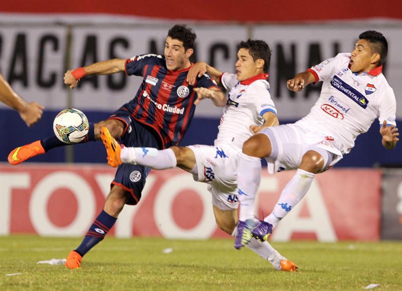 El jugador de San Lorenzo Mauro Matos (i) patea el balón ante la marca de Silvio Torales (c) y Raúl Píris (d), de Nacional. EFE