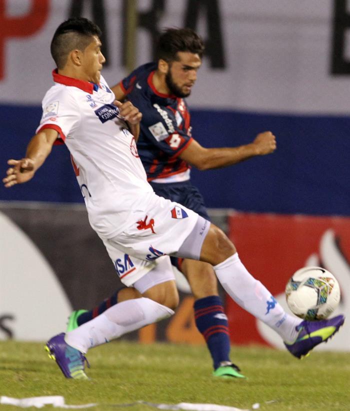 El jugador de San Lorenzo Julio Buffarini (frente) disputa el balón con Julián Benítez (atrás) de Nacional. EFE