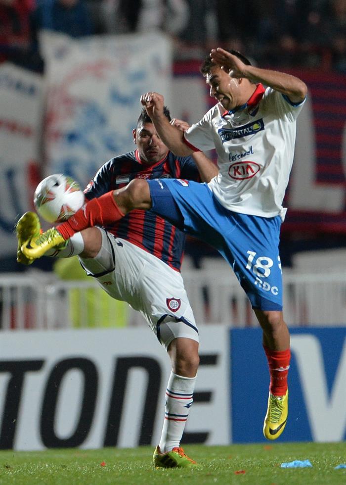 El jugador de San Lorenzo Néstor Ortigoza (i) disputa el balón con Derlis Orué (d), de Nacional. EFE