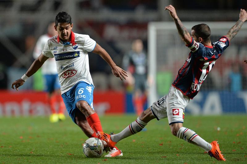 El jugador de San Lorenzo Leandro Romagnoli (d) disputa el balón con Silvio Torales (i), de Nacional. EFE