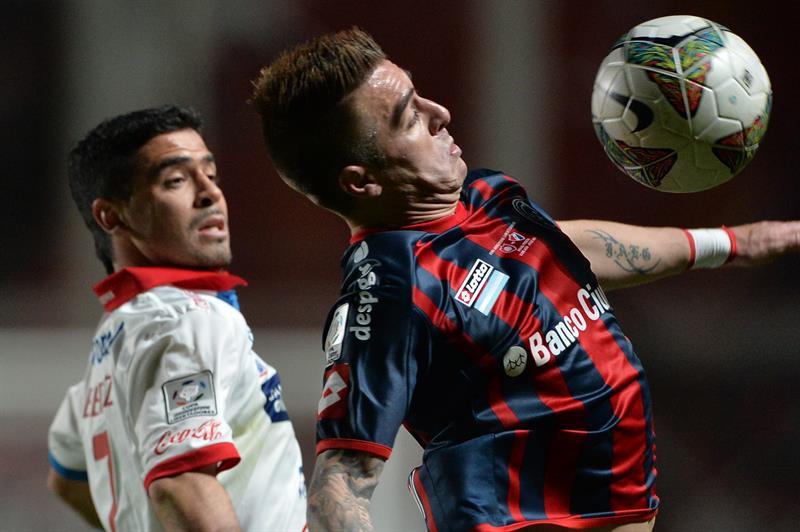 El jugador de San Lorenzo Julio Buffarini (d) recibe el balón ante la marca de Julián Benítez (i), de Nacional. EFE