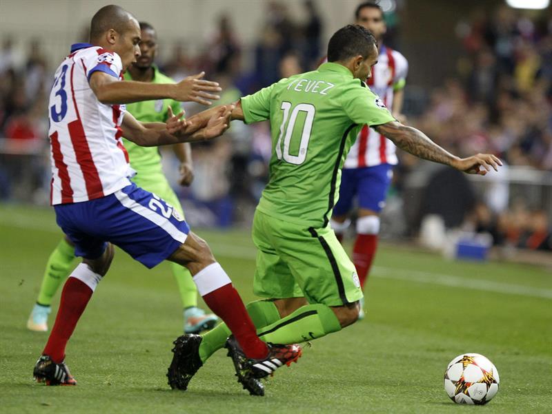 El defensa brasileño del Atlético de Madrid Joao Miranda (i) lucha el balón con el argentino Carlos Tévez, de la Juventus. Foto: EFE