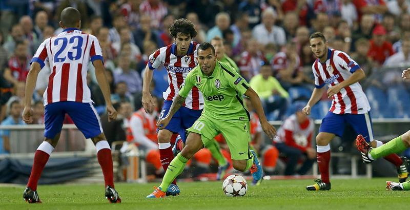 El delantero argentino del Juventus Carlos Tévez (c) con el balón ante varios jugadores del Atlético de Madrid Raúl García. Foto: EFE