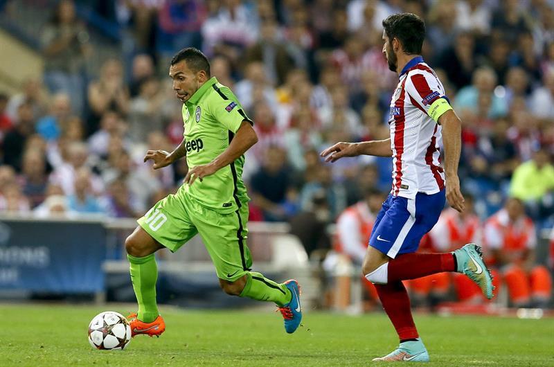 El delantero argentino del Juventus Carlos Tévez (i) con el balón ante el centrocampista del Atlético de Madrid Raúl García. Foto: EFE