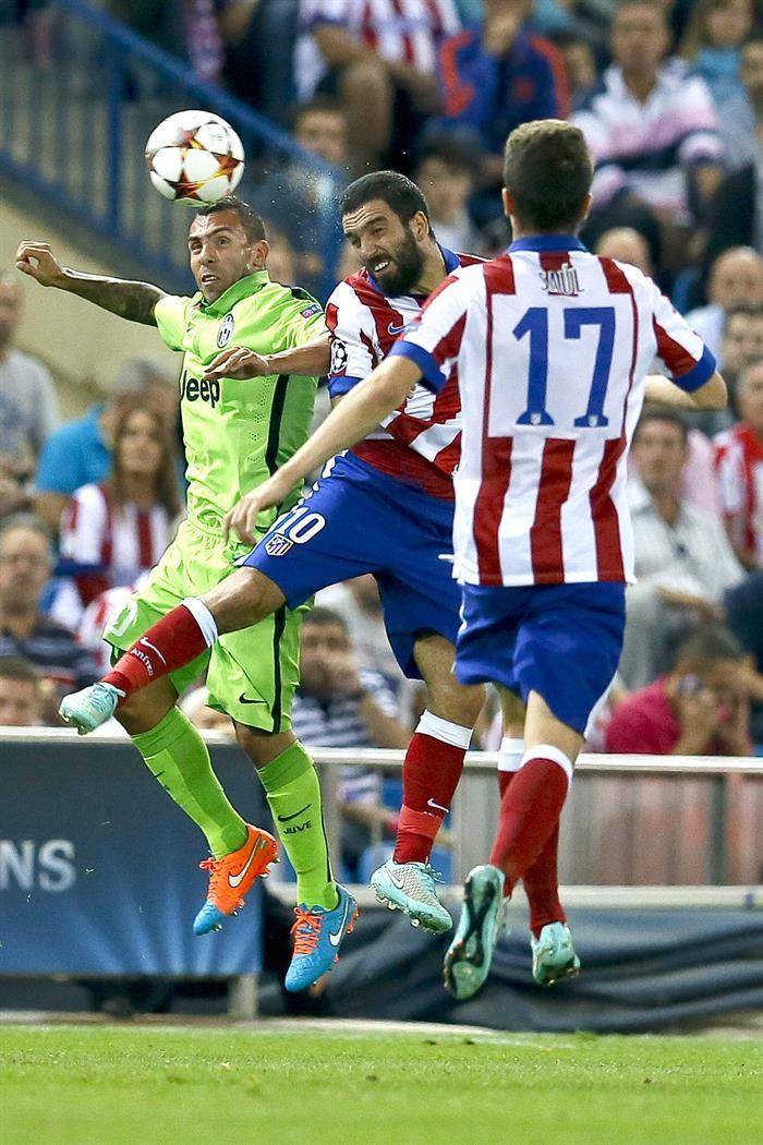 El centrocampista turco del Atlético de Madrid Arda Turan (c) salta por el balón con el argentino Carlos Tévez (i), de la Juventus. Foto: EFE