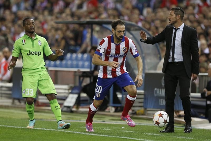 El defensa del Atlético de Madrid Juanfran Torres (d) recibe instrucciones de su entrenador, el argentino Diego Simeone (d), ante el defensa francés del Juventus Patricie Evra. Foto: EFE