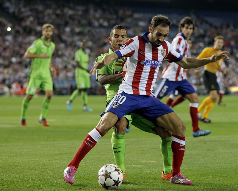 El defensa del Atlético de Madrid Juanfran (delante) lucha el balón con el argentino Carlos Tévez, de la Juventus. Foto: EFE